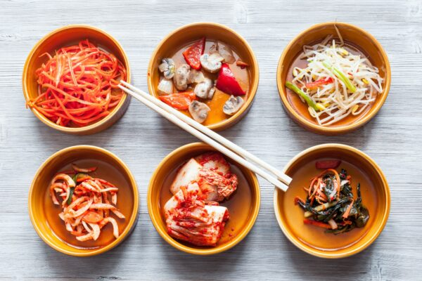 chopsticks above various appetizers in bowls